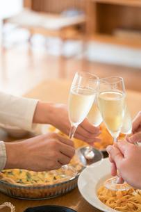 シャンパンで乾杯をする仲間の手元と料理の写真素材 [FYI01535471]
