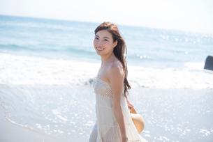 海の砂浜を素足で散歩する女性の写真素材 [FYI01535531]