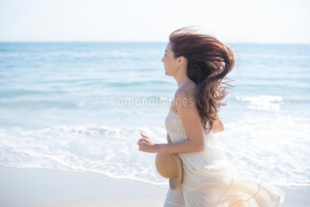 海の砂浜を素足で散歩する女性の写真素材 [FYI01535536]