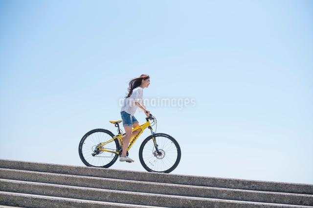 海の堤防を自転車で走る女性の写真素材 [FYI01535551]