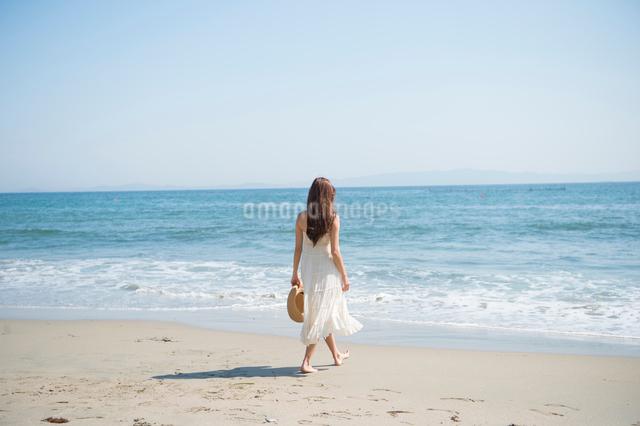 海の砂浜を素足で散歩する女性の写真素材 [FYI01535579]