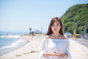 海の堤防を歩きスマホで音楽を聴く女性の写真素材 [FYI01535581]