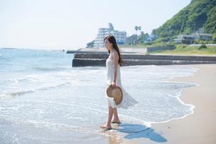 海の砂浜を素足で散歩する女性の写真素材 [FYI01535584]