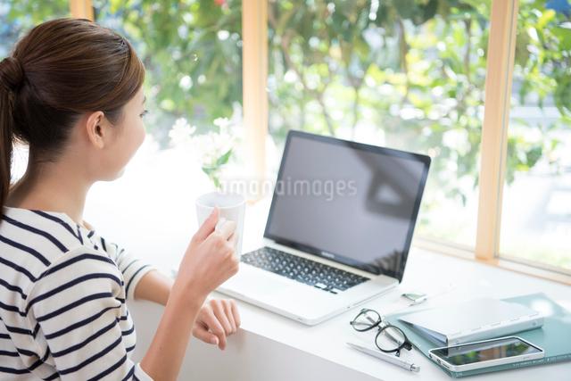 窓辺でパソコンをする女性の写真素材 [FYI01535590]