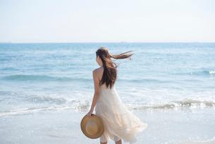 海の砂浜を素足で散歩する女性の写真素材 [FYI01535609]