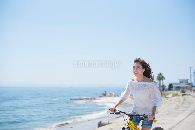海の堤防を自転車で走る女性の写真素材 [FYI01535613]