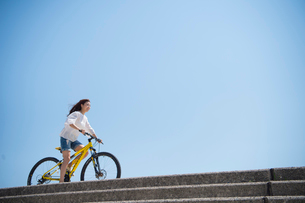 海の堤防を自転車で走る女性の写真素材 [FYI01535614]