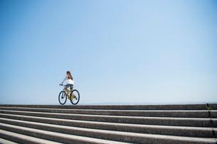 海の堤防を自転車で走る女性の写真素材 [FYI01535638]
