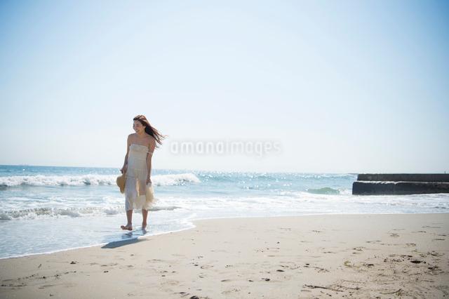 海の砂浜を素足で散歩する女性の写真素材 [FYI01535654]