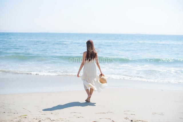 海の砂浜を素足で散歩する女性の写真素材 [FYI01535661]