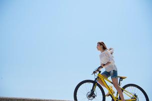 海の堤防を自転車で走る女性の写真素材 [FYI01535672]