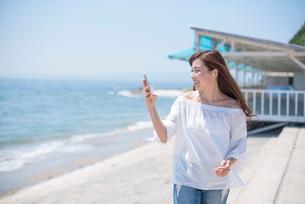 海の堤防を歩きスマホで音楽を聴く女性の写真素材 [FYI01535710]