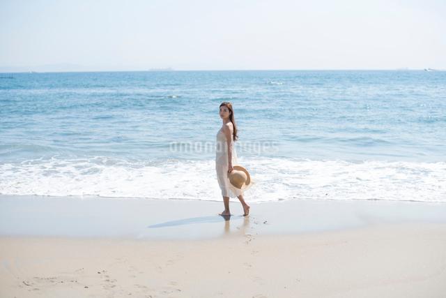 海の砂浜を素足で散歩する女性の写真素材 [FYI01535712]