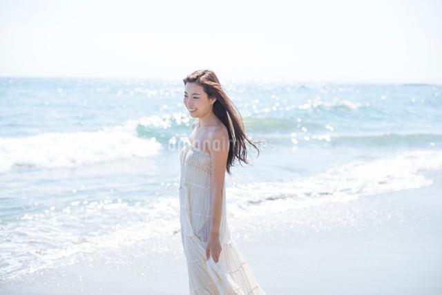 海の砂浜を素足で散歩する女性の写真素材 [FYI01535714]