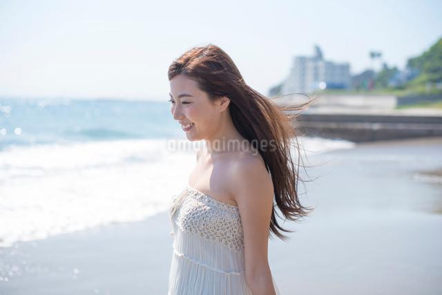 海の砂浜を素足で散歩する女性の写真素材 [FYI01535729]