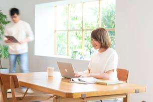 PCでテレワークの20代女性と夫の写真素材 [FYI01535736]