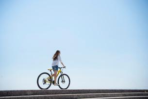 海の堤防を自転車で走る女性の写真素材 [FYI01535738]