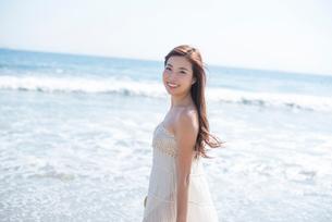 海の砂浜を素足で散歩する女性の写真素材 [FYI01535746]