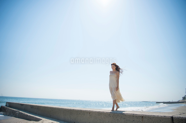海の砂浜を素足で散歩する女性の写真素材 [FYI01535772]
