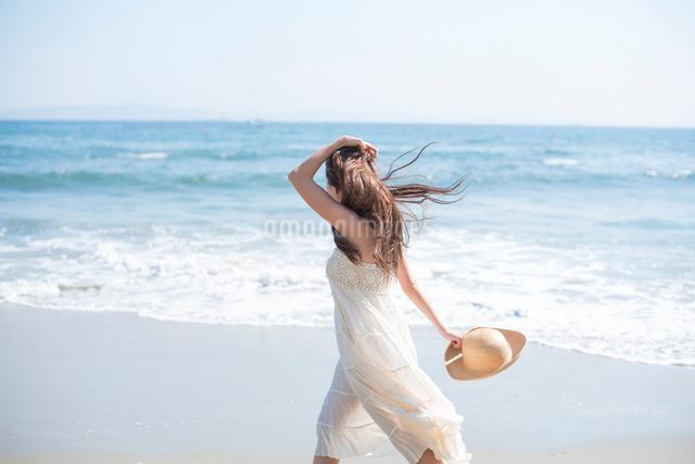 海の砂浜を素足で散歩する女性の写真素材 [FYI01535774]