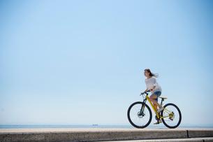 海の堤防を自転車で走る女性の写真素材 [FYI01535802]