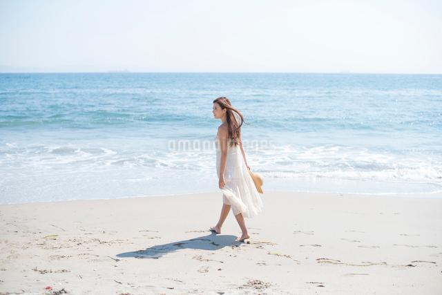 海の砂浜を素足で散歩する女性の写真素材 [FYI01535803]