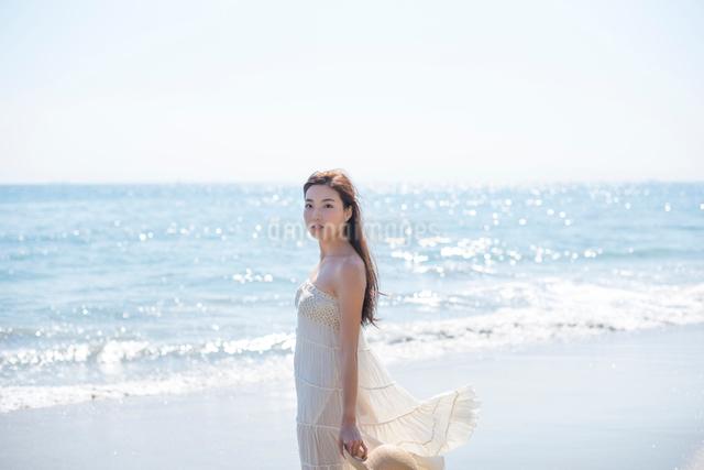 海の砂浜を素足で散歩する女性の写真素材 [FYI01535808]