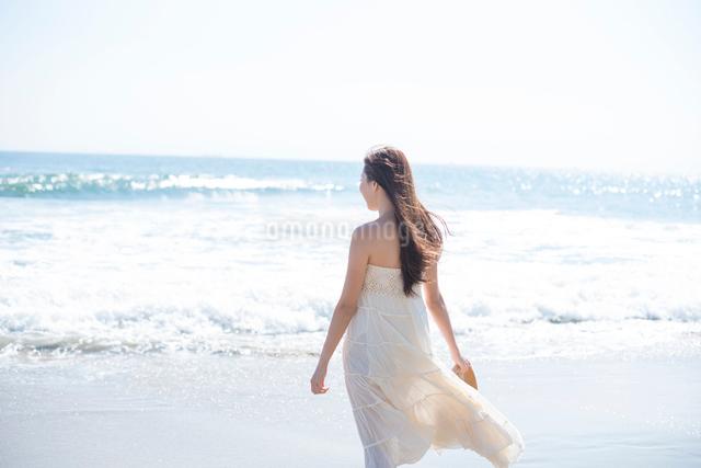 海の砂浜を素足で散歩する女性の写真素材 [FYI01535823]