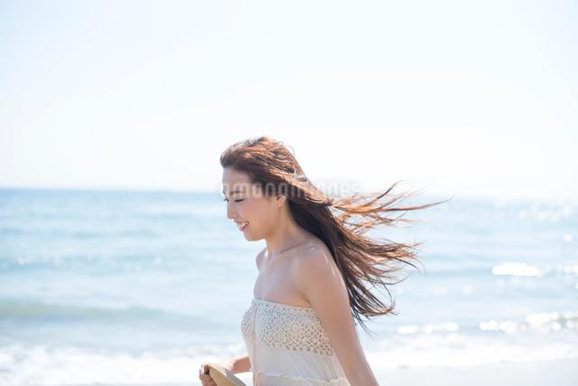 海の砂浜を素足で散歩する女性の写真素材 [FYI01535825]