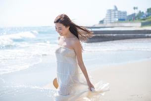 海の砂浜を素足で散歩する女性の写真素材 [FYI01535842]