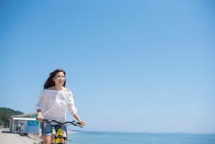 海の堤防を自転車で走る女性の写真素材 [FYI01535853]