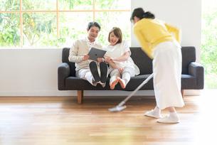 掃除する女性とソファでPCを見る父と娘の写真素材 [FYI01536060]