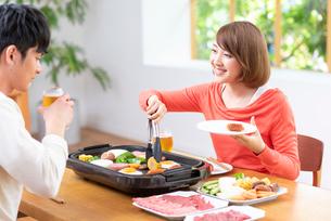 生ビールで焼肉を食べる20代夫婦の写真素材 [FYI01536064]