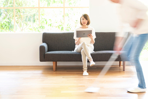 掃除する男性とソファでPCを見る20代女性の写真素材 [FYI01536067]
