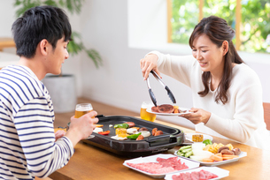 生ビールで焼肉を食べる30代夫婦の写真素材 [FYI01536071]