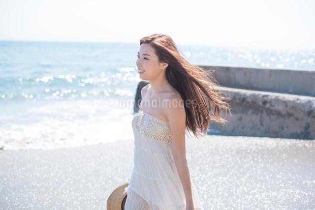 海の砂浜を素足で散歩する女性の写真素材 [FYI01536126]