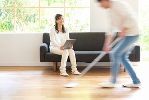 掃除する男性とソファでPCを見る30代女性の写真素材 [FYI01536243]