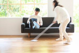 掃除する女性とソファでPCを見る30代男性の写真素材 [FYI01536278]