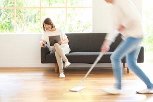 掃除する男性とソファでPCを見る20代女性の写真素材 [FYI01536291]