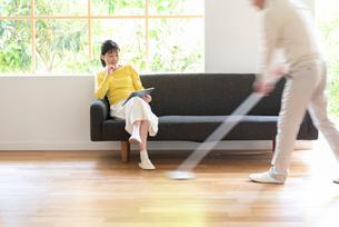 掃除する男性とソファでPCを見る中高年女性の写真素材 [FYI01536334]