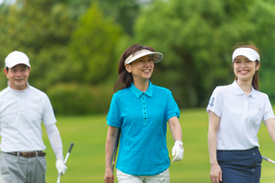 ゴルフをする三人家族の写真素材 [FYI01536344]