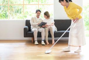 掃除する女性とソファでPCを見る父と娘の写真素材 [FYI01536368]