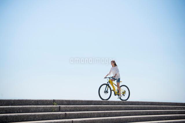 海の堤防を自転車で走る女性の写真素材 [FYI01536427]