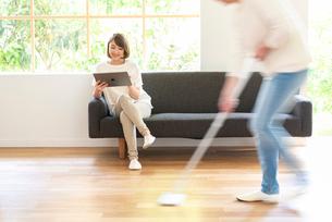 掃除する男性とソファでPCを見る20代女性の写真素材 [FYI01536433]