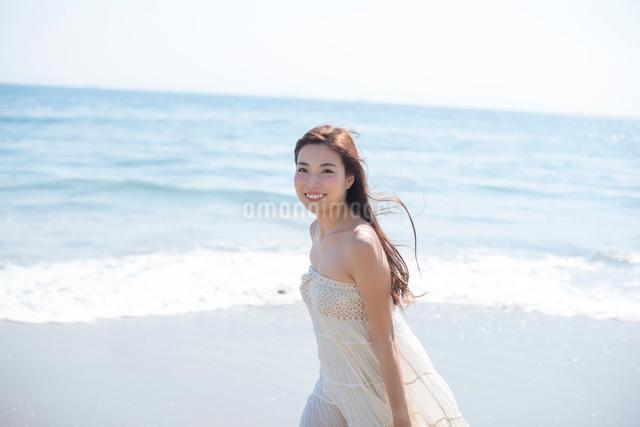 海の砂浜を素足で散歩する女性の写真素材 [FYI01536477]