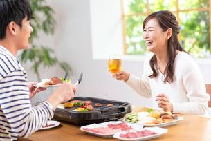 生ビールで焼肉を食べる30代夫婦の写真素材 [FYI01536481]