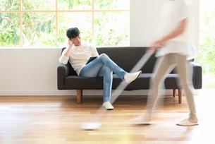 掃除する女性とソファでPCを見る20代男性の写真素材 [FYI01536488]