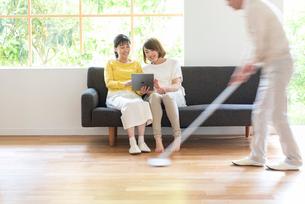 掃除する男性とソファでPCを見る母と娘の写真素材 [FYI01536559]