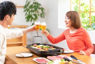 生ビールで乾杯し焼肉を食べる20代夫婦の写真素材 [FYI01536696]