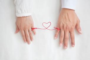 男女の指と指を結んだ赤い糸の写真素材 [FYI01536953]